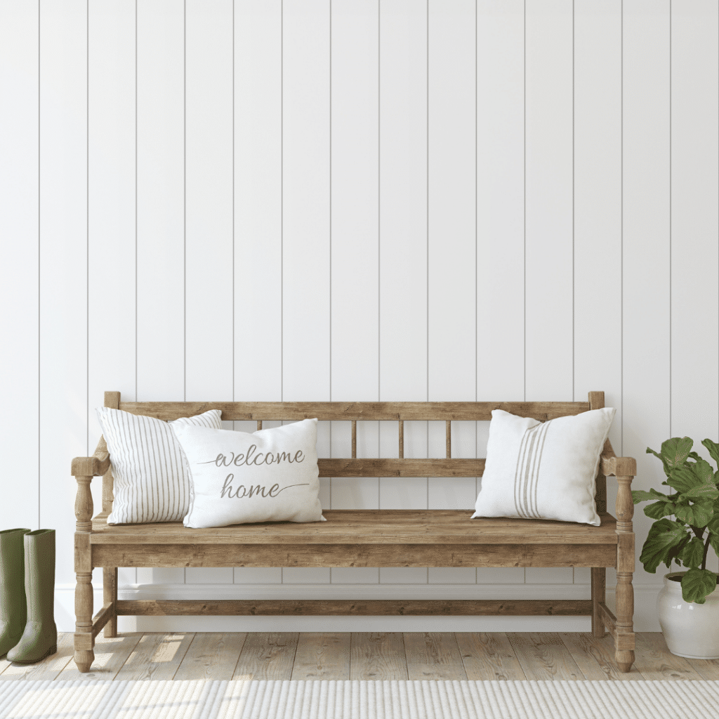 Illustrating the organization idea of the usefulness of a bench in the entryway. A wooden bench with three pillows in the entryway of a home.