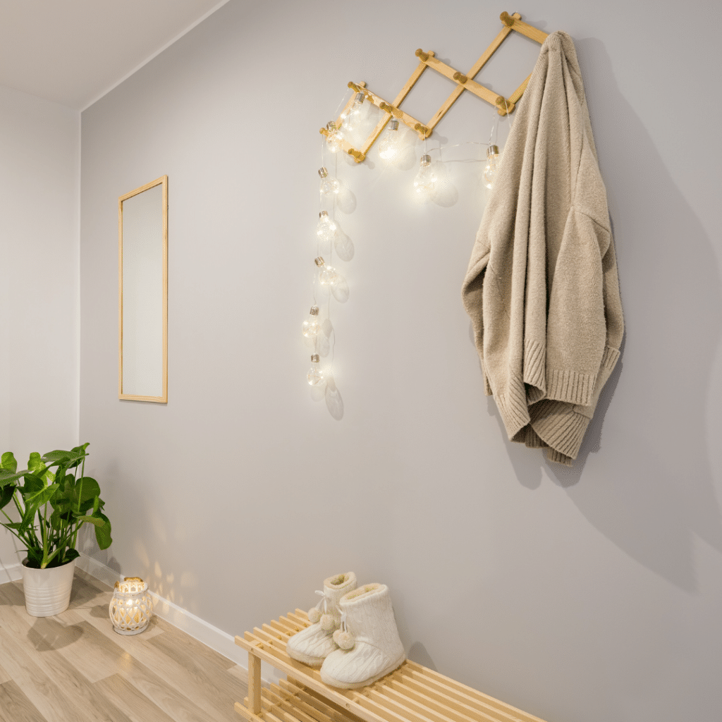 Illustrating the organizational idea that wall hooks can create storage space and personality in an entryway. Wall hooks are strung with lights in a light-colored entryway.